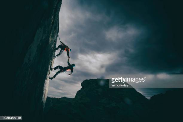 helping a friend up - mountain climbing stock pictures, royalty-free photos & images