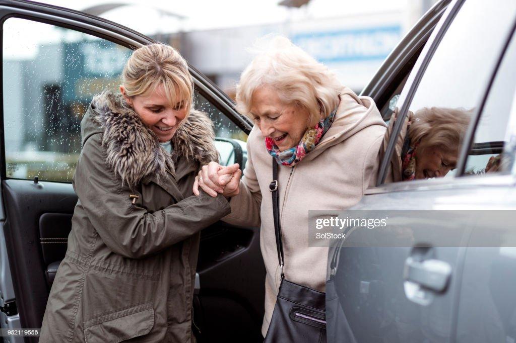 Eine ältere Frau aus dem Auto zu helfen : Stock-Foto