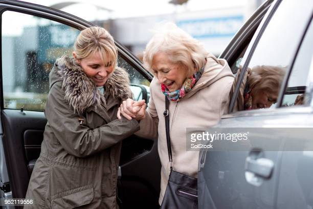 helping a senior woman out of the car - sostegno morale foto e immagini stock