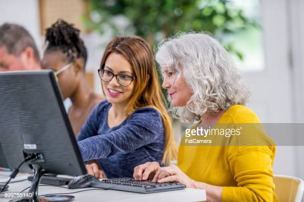 helping a woman using a computer - adult stock pictures, royalty-free photos & images