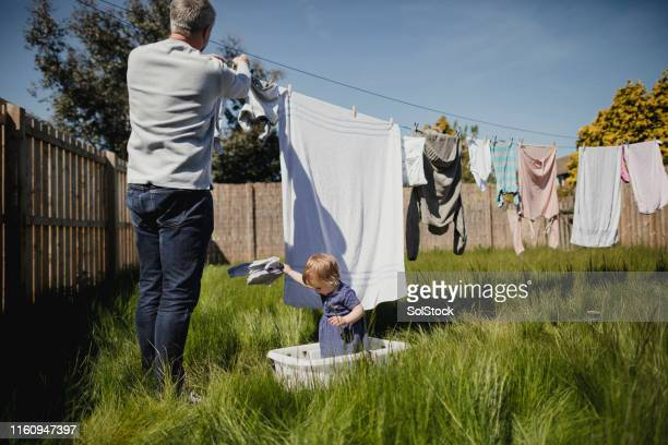 helping dad with the housework - clothesline stock pictures, royalty-free photos & images