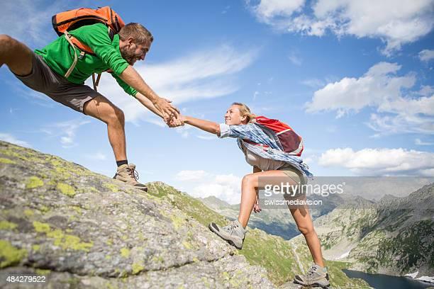 Aider la main entre deux grimpeur-été
