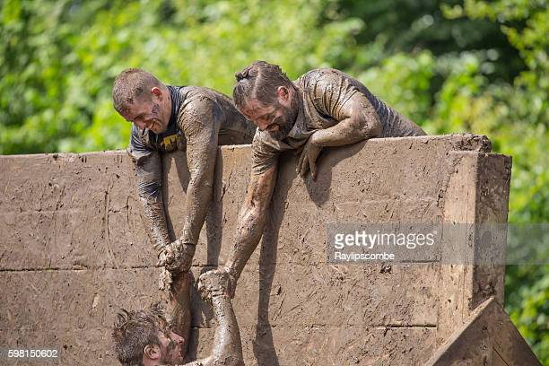 helping hand to climb a slippery wall - obstacle course stock photos and pictures