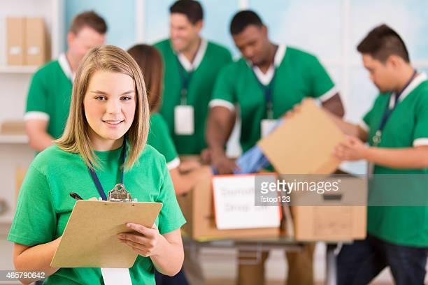 Helfende Hände! Junger Erwachsener Freiwilligen, die Kleidung Spenden sammeln.
