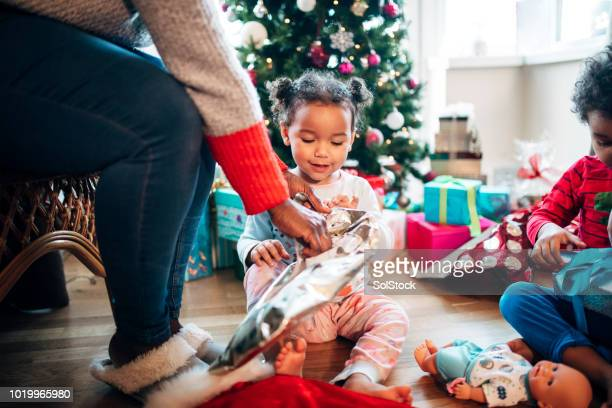 Helping her Daughter Open Presents on Christmas Morning