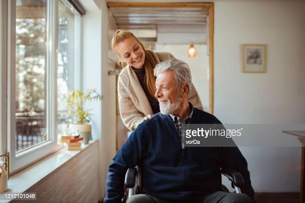 het helpen van haar oude mens - hulp stockfoto's en -beelden