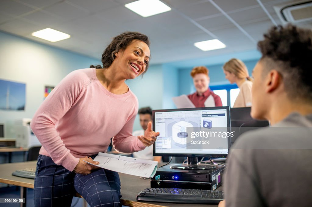 Helping her Student with his Project : Stock Photo