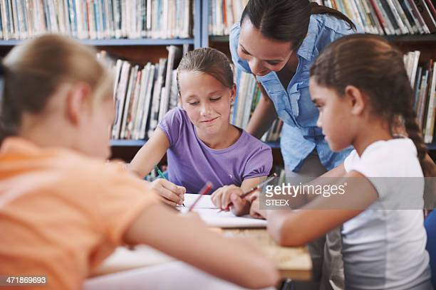 helping her students grasp the work - teacher bending over stock photos and pictures