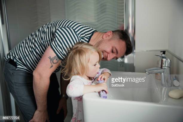 helping his daughter brush her teeth - electric toothbrush stock pictures, royalty-free photos & images