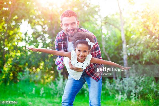 helping his daughter fly! - black man holding baby stock photos and pictures