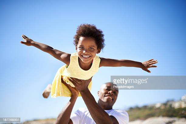 helping his daughter soar! - candid beach stock photos and pictures