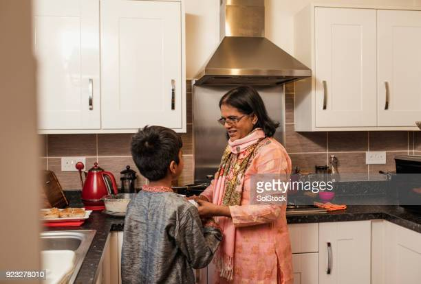 helping his grandmother in the kitchen - muslim boy stock photos and pictures