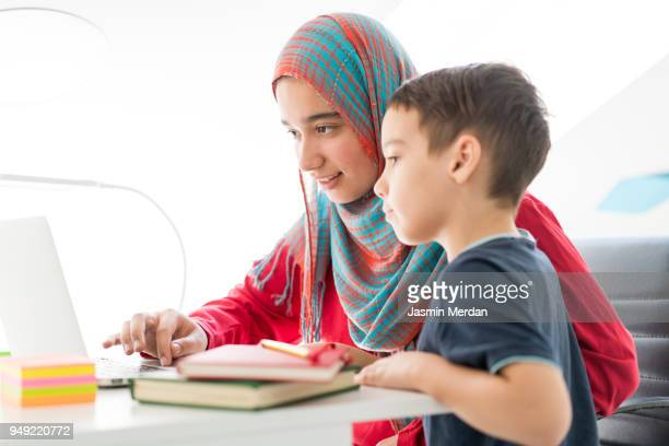 Helping little boy in studying at home