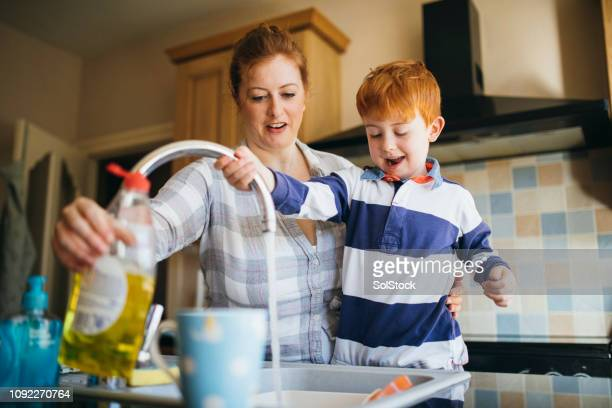 helping mum wash the dishes - dishwashing liquid stock photos and pictures