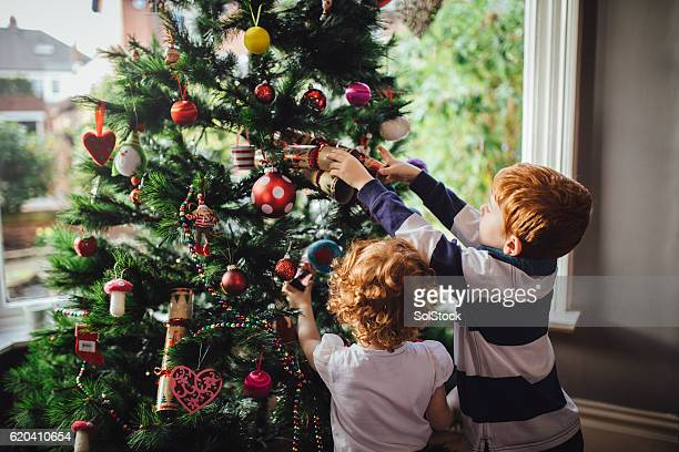 helping mum with the tree - christmas tree stock pictures, royalty-free photos & images