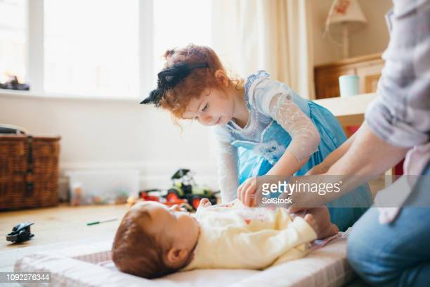 helping mummy change her baby sister's nappy - baby changing mat stock pictures, royalty-free photos & images