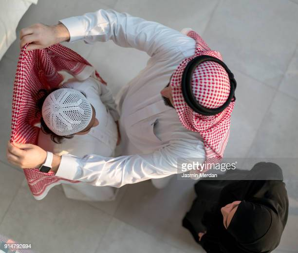 Helping son to wear clothes