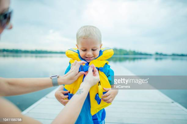 ayudar a hijo con chaleco salvavidas - life jacket photos fotografías e imágenes de stock