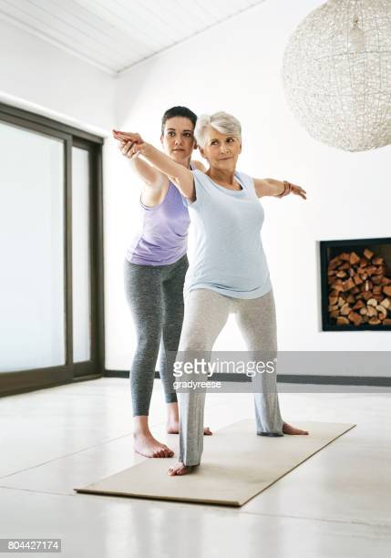 helping to perfect her form and posture - yoga teacher stock pictures, royalty-free photos & images