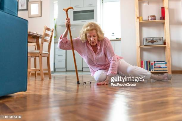 helpless retired woman with blonde hair sitting on floor at home.the risks that come with getting older. - falling stock pictures, royalty-free photos & images
