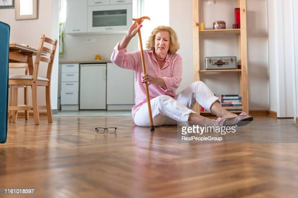 helpless retired woman with blonde hair sitting on floor at home.the risks that come with getting older. - osteoporosis stock pictures, royalty-free photos & images