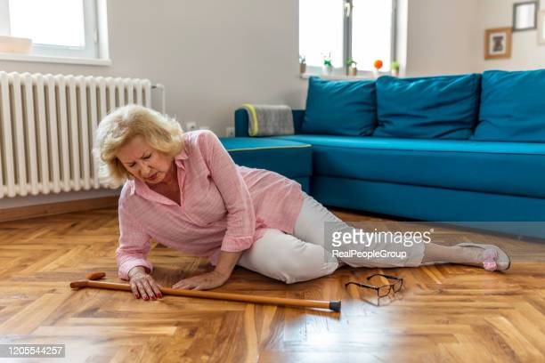 hilflose rentnerin mit blonden haaren sitzt zu hause auf dem boden. die risiken, die mit dem älterwerden verbunden sind. - fallen stock-fotos und bilder