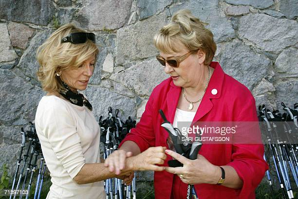 Spanish Health and Consumer Minister Elena Salgado is shown how to use nordic walking sticks by Finnish Health and Social Services Minister Liisa...