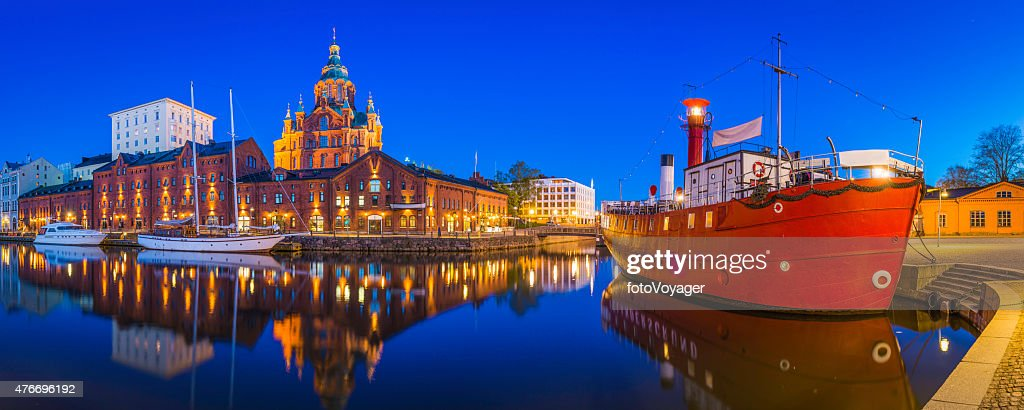 Helsinki Uspenski Cathedral overlooking tranquil waterfront harbour illuminated dusk Finland : Stock Photo