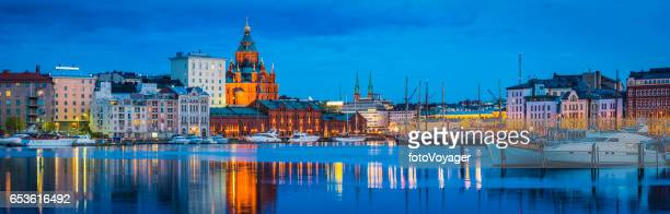 Helsinki Uspenski Cathedral overlooking waterfront marina illuminated dusk panorama Finland