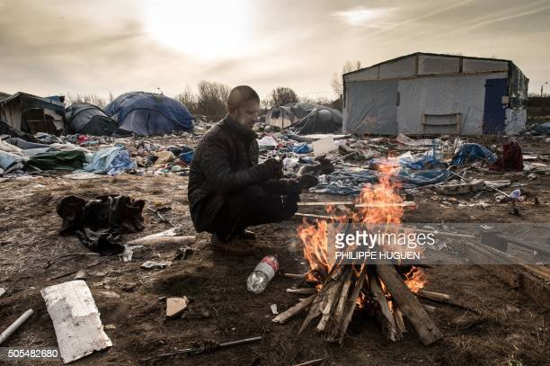 Hemn a Kurd migrant keeps warm next to a fire on a makeshift camp known as the jungle on January 18 2016 in Calais The residents of the camp in the...