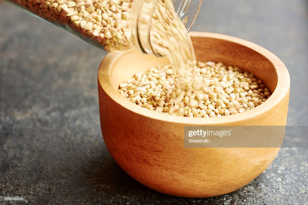 Hemp seeds being poured into a wooden bowl : Foto de stock