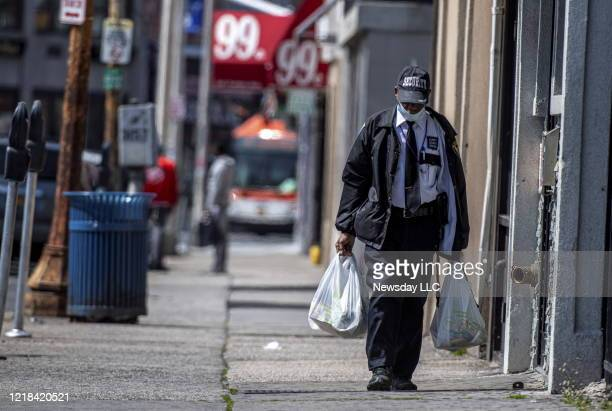 A man wearing a security guard uniform and a mask due to coronavirus concerns walks down a street carrying groceries in Hempstead New York on April 8...