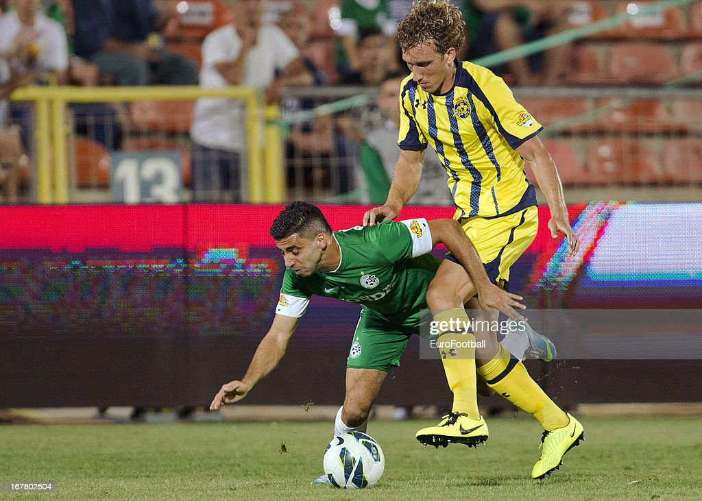 Hen Ezra (L) of Maccabi Haifa FC is challenged by Ignacio Fideleff of Maccabi Tel-Aviv FC during the Israeli Premier League match between Maccabi Haifa FC and Maccabi Tel-Aviv FC held on April 29, 2013 at the Kiryat Eliezer Stadium in Haifa, Israel.
