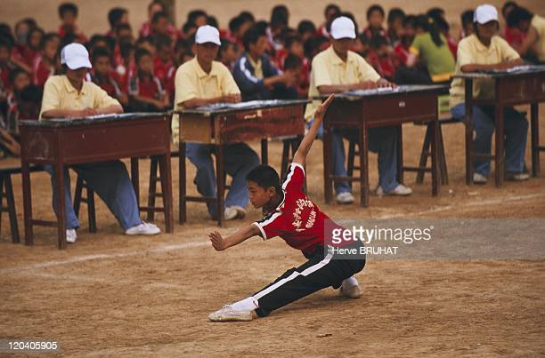 Henan in China in June, 2005 - Kung-fu school competition. The student executes a sequences of movements . There are more than 400 such trainings,...