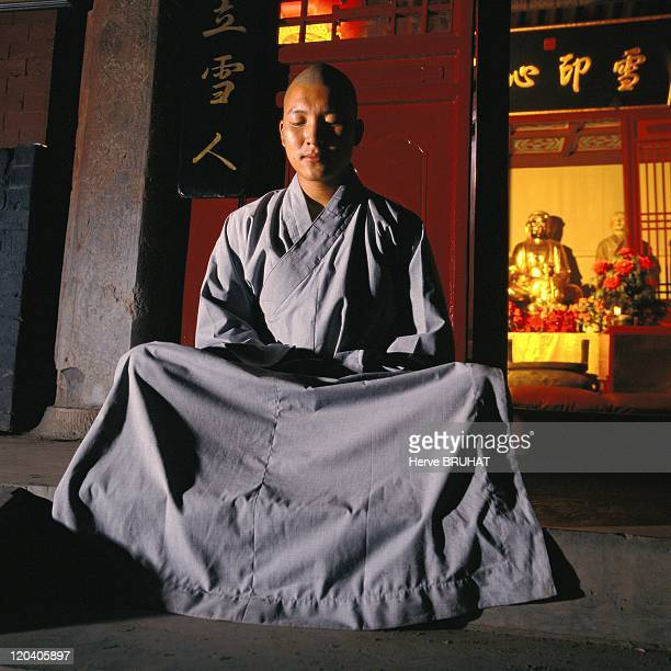 Henan in Shaolin China A monk practicing meditation The word chan means meditation The adept is seated holding himself immobile his back straight and...