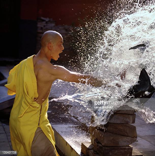 Henan in Shaolin, China - Exercise of hard qigong. With a single movement of the palm of the hand, the adept is able to break a jar filled with ice....