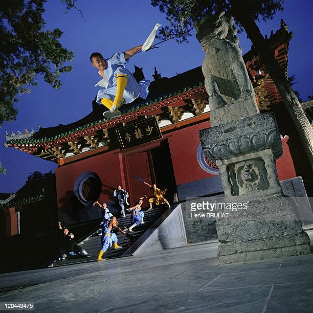 Henan in Shaolin, China - Night session in front of the entrance of the Shaolin Temple. In the foreground the adept is armed with a combat sword...