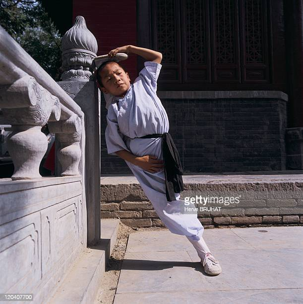 Henan in Shaolin, China - Session of stretching exercises before a martial arts course. The young student in martial arts consecrates at least a...