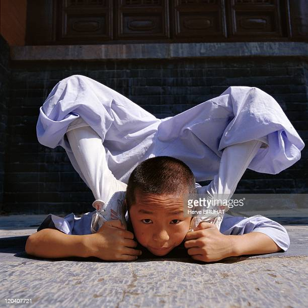 Henan in Shaolin, China - Shi Xia Peng, nine years old, from Henan province, is practicing the tongzi gong on the temple terrace. The tongzi gong...