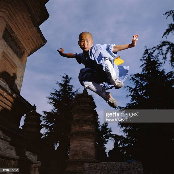 Henan in Shaolin, China - ShiXiao Qun, ten years old, from Anhui province, performing a leap in the Forest of Pagodas. His hands are in the position...
