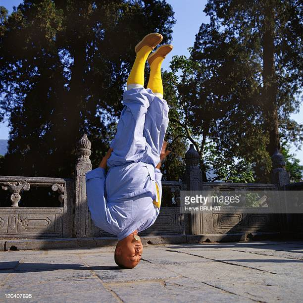 Henan in Shaolin, China - The monk Shi Yan Zheng on the temple terrace executing a very advanced variant of tongzi gong: the posture on the head...