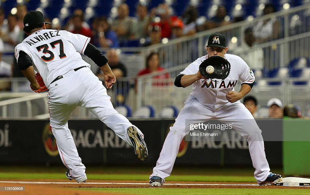 Henderson Alvarez #37 of the Miami Marlins scoops the ball to Logan Morrison #5 during a game against the New York Mets at Marlins Park on July 31, 2013 in Miami, Florida.