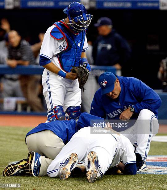 Henderson Alvarez of the Toronto Blue Jays is looked over by JP Arencibia and Manager John Farrell after being hit by a ball while covering home...
