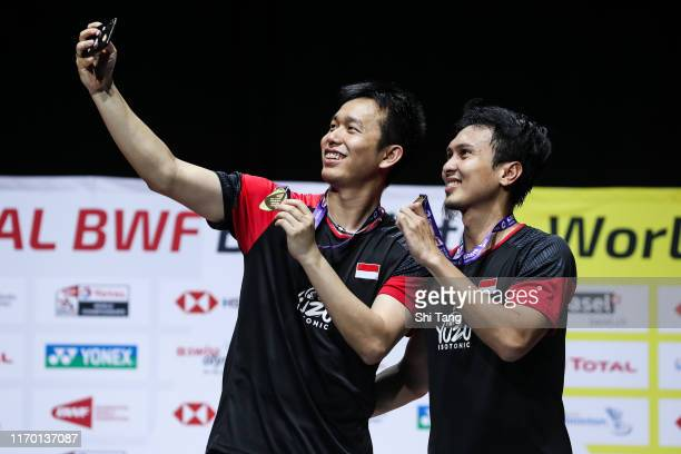 Hendra Setiawan and Mohammad Ahsan of Indonesia take selfie with their medals on the podium for the men's doubles event during day seven of the Total...