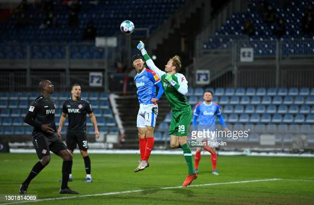 Hendrik Bonmann of Würzburger Kickers punches the ball away from Lee Jae-Song of Holstein Kiel leading to a penalty during the Second Bundesliga...