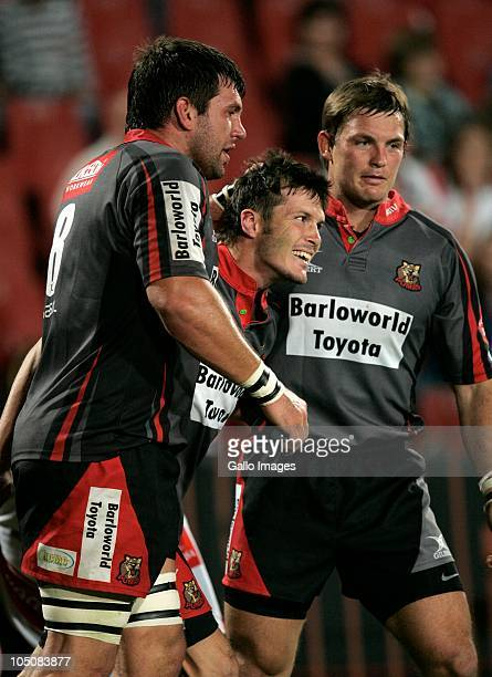 Hendrik van der Nest is congratulated by team mates Doppies Le Roux and Johan Jackson after scoring for the Pumas during the Absa Currie Cup match...