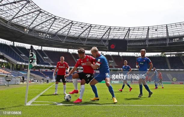 Hendrik Weydandt of Hannover 96 is challenged by Sebastian Griesbeck of 1. FC Heidenheim 1846 during the Second Bundesliga match between Hannover 96...