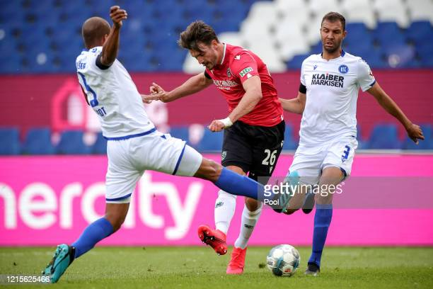 Hendrik Weydandt of Hannover is challenged by David Pisot and Daniel Gordon of Karlsruhe during the Second Bundesliga match between Hannover 96 and...