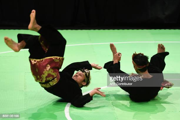 Hendy and Yolla Primadona Jumpil of Indonesia perform during the Pencak Silat double final at the 29th Southeast Asian Games in Kuala Lumpur on...