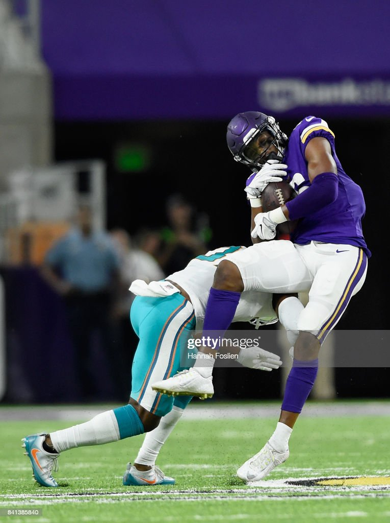 A.J. Hendy #37 of the Miami Dolphins tackles Cayleb Jones #16 of the Minnesota Vikings during the fourth quarter in the preseason game on August 31, 2017 at U.S. Bank Stadium in Minneapolis, Minnesota. The Dolphins defeated the Vikings 30-9.